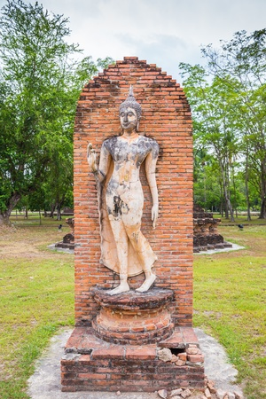Walking Buddha statue in Sukhothai Historical Park, Thailand photo