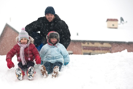 Father and sons having fun on the snow