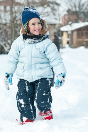 Portrait of young kid walking in the snow