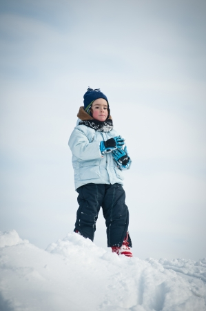 Young kid portrait in the snow against cloudy blue sky
