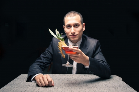 Elegant young man drinking cocktail on black background