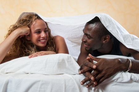 Interracial young happy couple relaxed in bed