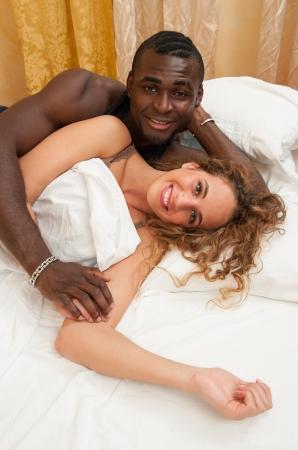 interracial marriage: Interracial giovane coppia felice disteso a letto Archivio Fotografico