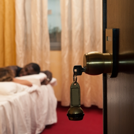 Hotel s door with key, with young couple relaxing in bed in the background