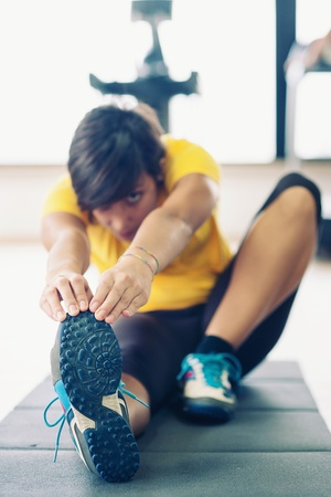 Young woman stretching her leg to warm up in the gym Stock Photo - 17505745