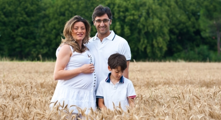 Happy family relaxing in a wheat field   Stock Photo - 17505746