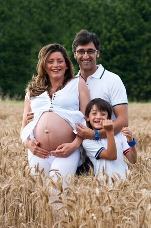 Happy family relaxing in a wheat field   photo