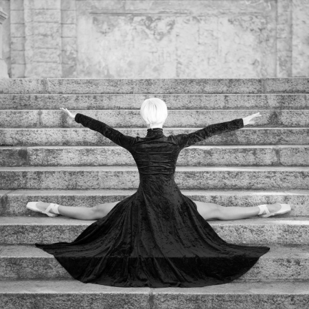 Jonge mooie ballerina met zwarte lange jurk poseren op Pincio trappen, Bologna, Italië. Ballerina project.