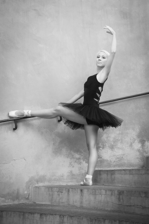 Young beautiful ballerina posing sit on the stairs  Black and white image  Ballerina project   Stock Photo