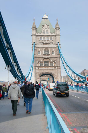 LONDON - APRIL 10, 2014: People walking on Tower Bridge. The Tower Bridge (built 1886-1894) is a combined bascule and suspension bridge with a total length of 244 metres (801 ft).
