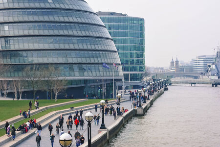 LONDON - APRIL 10, 2014: People walking close to City Hall. The building has a bulbous shape to reduce its surface area and improve energy efficiency.  Editorial