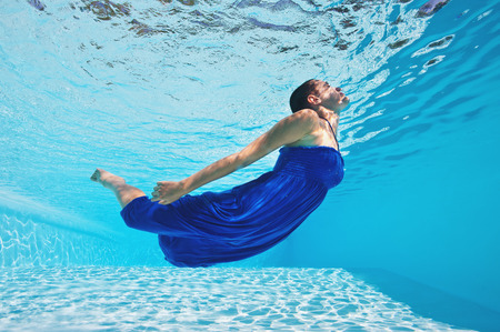 Underwater woman portrait with blue dress in swimming pool
