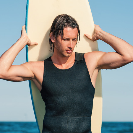 Young handsome man portrait at the sea with surfboard