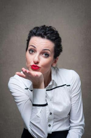 Business woman portrait sending a kiss on grunge background  Stockfoto