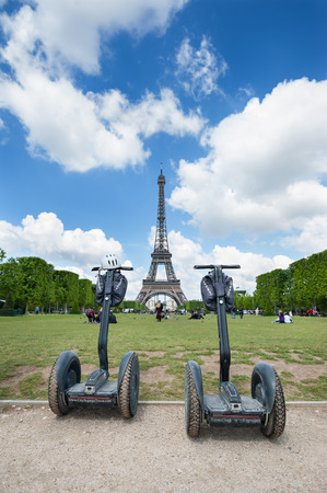 a two wheeled vehicle: PARIS, FRANCE - MAY 14, 2014  Segway parked in front the Eiffel Tower in Paris  The Segway is a two-wheeled, self-balancing, battery-powered electric vehicle