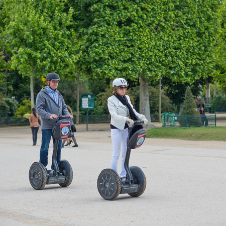 PARIS, FRANCE - MAY 14, 2014  Tourists visiting the city near the Eiffel Tower during their guided Segway tour of Paris