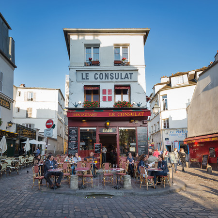 PARIS, FRANCE - MAY 15, 2014  Tourists walking in front of Le Consulat, a typical cafe in Montmartre area