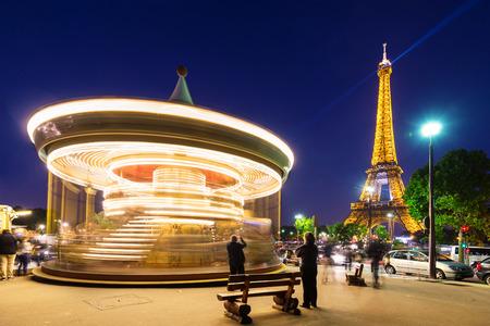PARIS, FRANCE - MAY 17, 2014  Illuminated vintage carousel close to Eiffel Tower, Paris
