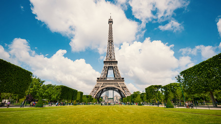 Eiffel Tower and gardens with people walking against blue cloudy sky. Paris, France.