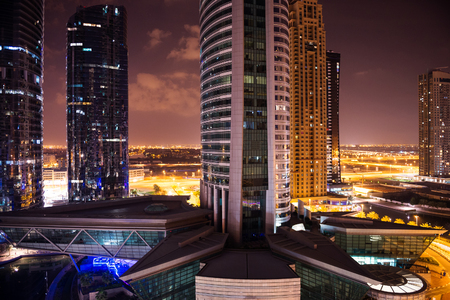 DUBAI, UAE - MARCH 27, 2014: Buildings of Jumeirah Lakes Towers at night. The JLT is a large development which consists of 79 towers being constructed along the edges of 4 artificial lakes.