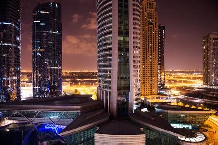 DUBAI, Verenigde Arabische Emiraten - 27 maart 2014: Gebouwen van de Jumeirah Lakes Towers 's nachts. De JLT is een grote ontwikkeling bestaande uit 79 torens gebouwd langs de randen van 4 kunstmatige meren. Redactioneel