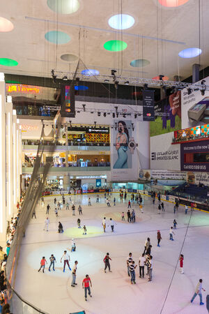 DUBAI, UAE - MARCH 28, 2014: People having fun inside the ice rink of the Dubai Mall. At over 12 million sq ft, it is the world's largest shopping mall.