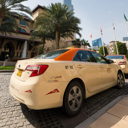 DUBAI, UAE - MARCH 30, 2014: Taxi car parked outside Palace Hotel. Dubai has an extensive taxi system, by far the most frequently used means of public transport within the Emirates.