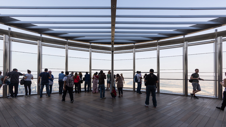 DUBAI, UAE - MARCH 30, 2014: People on Burj Khalifa observation terrace. Burj Khalifa is the tallest man-made structure in the world, at 829.8 m (2,722 ft).