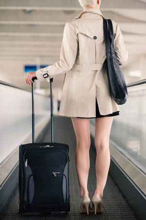 Businesswoman portrait with trolley at Charles de Gaulle airport, Paris.