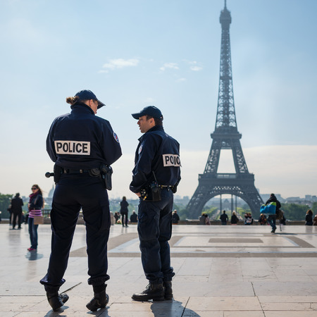 police icon: PARIS, FRANCE - MAY 14, 2014: National Police in front of the Eiffel Tower. The National Police comes under the jurisdiction of the Ministry of the Interior and has about 150,000 employees.