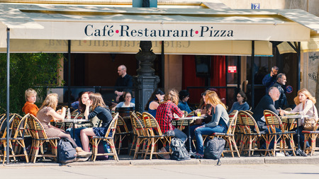 파리, 프랑스 - 2014년 5월 16일 : 관광객 전통적인 파리의 카페에 앉아있다. 파리에서 약 40,000 곳의 레스토랑이 있습니다.