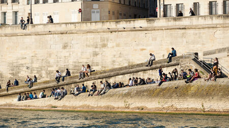 PARIS, FRANCE - MAY 16, 2014: People relax on the river Seine at sunset.