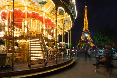 PARIS, FRANCE - MAY 17, 2014: Illuminated vintage carousel close to Eiffel Tower, Paris.