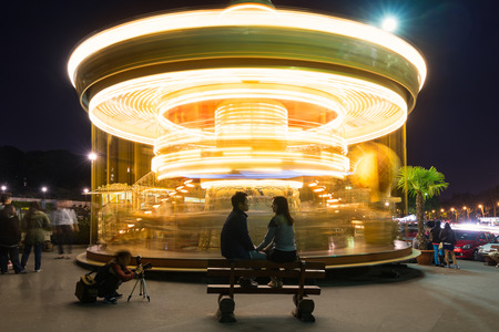 PARIS, FRANCE - MAY 17, 2014: Couple of spouses in front of Illuminated vintage carousel close to Eiffel Tower, Paris.
