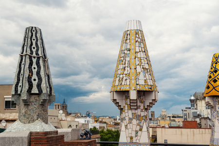 BARCELONA, SPAIN - MAY 31, 2014: Colourful chimneys on rooftop of Gaudis masterpiece Palau Guell. One of the earliest Gaudis masterpieces, UNESCO heritage site.