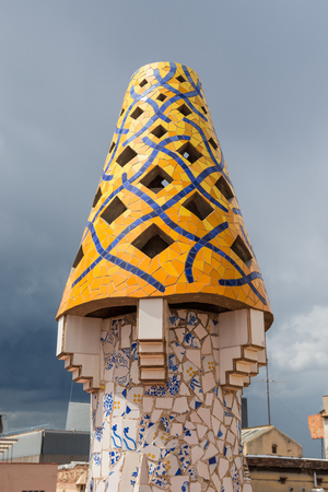 BARCELONA, SPAIN - MAY 31, 2014: Colourful chimney on rooftop of Gaudi's masterpiece Palau Guell. One of the earliest Gaudi's masterpieces, UNESCO heritage site.