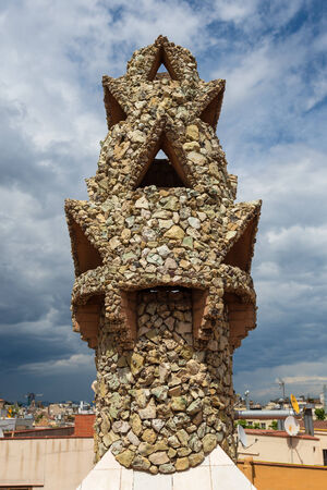 BARCELONA, SPAIN - MAY 31, 2014: Colourful chimney on rooftop of Gaudis masterpiece Palau Guell. One of the earliest Gaudis masterpieces, UNESCO heritage site. Editorial