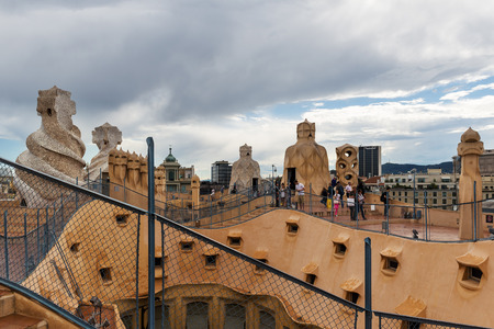 BARCELONA, SPAIN - MAY 31, 2014: Tourists on rooftop of Gaudis masterpiece Casa Batlo. The building that is now Casa Batllo was built in 1877 by Antoni Gaudi, commissioned by Lluis Sala Sanchez.