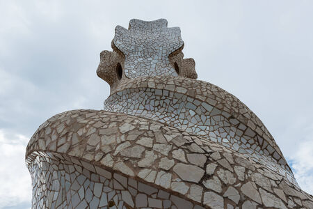 BARCELONA, SPAIN - MAY 31, 2014: Chimney on rooftop of Gaudis masterpiece Casa Batlo. The building that is now Casa Batllo was built in 1877 by Antoni Gaudi, commissioned by Lluis Sala Sanchez.