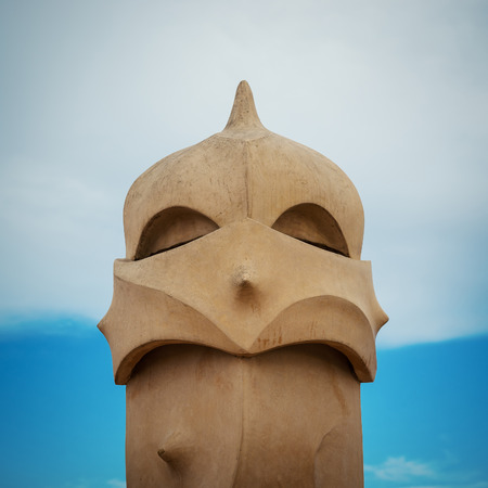 commissioned: BARCELONA, SPAIN - MAY 31, 2014: Chimney on rooftop of Gaudis masterpiece Casa Batlo. The building that is now Casa Batllo was built in 1877 by Antoni Gaudi, commissioned by Lluis Sala Sanchez.