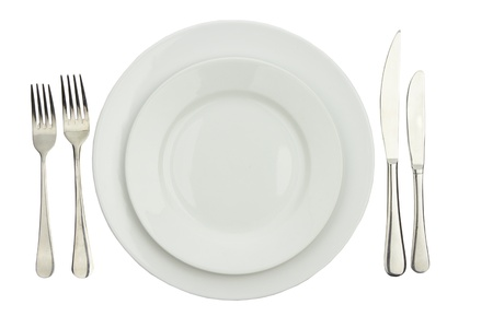 Place setting with high-gloss plate, knife & fork. Isolated on white.  Stock Photo