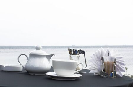 Cup of tea and teapot on table on seacoast photo