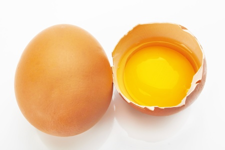 yolk: Two brown eggs on a white background. One egg is broken.