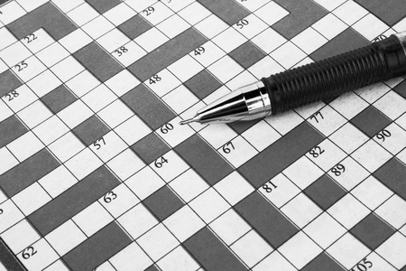pen lying on a blank crossword to be filled  Stock Photo