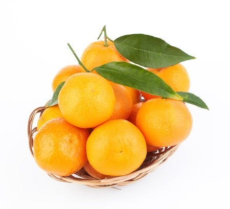 tangerines with leaves in a beautiful basket  on white photo