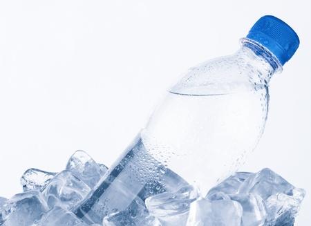 Water fles in ijs op een witte achtergrond Stockfoto