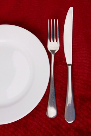 dinning: White plate, fork and knife on red background.  Stock Photo
