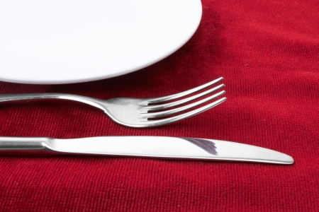 White plate fork and knife on red background. Stock Photo - 13628207