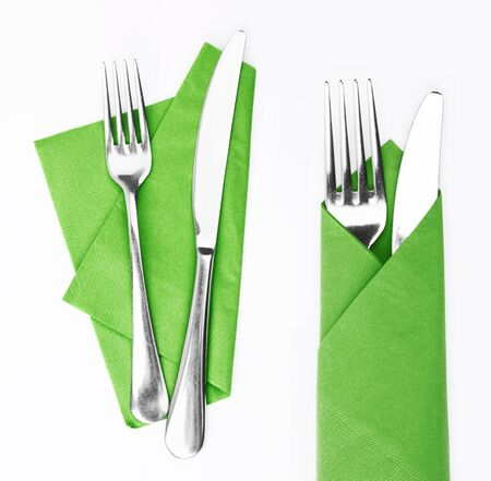 Fork and knife in a green cloth isolated on white photo