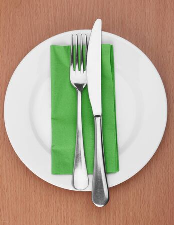 Fork and knife in a green cloth on white photo